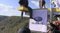 Base jumper gets ready to jump and leaps from platform Stock Footage