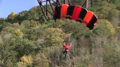 Jumper with black and red parachute landing smoothly in the water Stock Footage