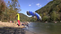 Jumper landing at edge of water and parachute covering him Stock Footage