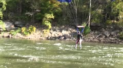 Two base jumpers, one landing in the water and one landing on the beach - stock footage