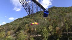 Lady base jumper landing in the water at the edge of the New River Stock Footage