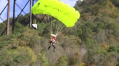 Base Jumper with bright green parachute landing at the edge of the water Stock Footage