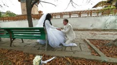 Newlyweds on  bench in autumn park Stock Footage