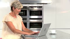 Mature Lady with Laptop in Kitchen Stock Footage