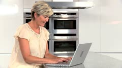 Middle Aged Lady with Laptop in Kitchen Stock Footage