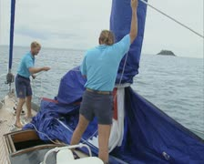People on boat raising sail Stock Footage