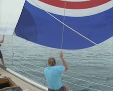 People on boat raising and securing sail Stock Footage