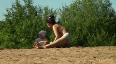 Mother and daughter sunbathe on the sand Stock Footage