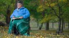 Senior woman reading outdoors - stock footage