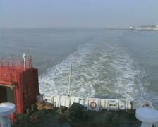 Rear view from travelling ferry with view of coastal town Stock Footage
