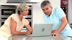 Mature Couple Using Wireless Latop in Home Kitchen - stock footage
