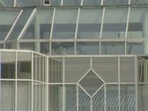Stock Video Footage of Zoom out from building with glass conservatory roofs and windows