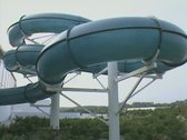 View of bends in water park swimming chute with people sliding through Stock Footage