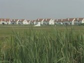 Panning view across field of row of houses Stock Footage