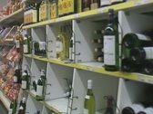 Stock Video Footage of Travelling shot inside convenience store moving past wine section