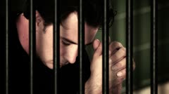 Man sitting in jail cell - stock footage