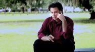Man talking on phone outside at a park Stock Footage