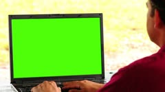 Man using laptop key green over shoulder Stock Footage