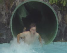 Close up view of bottom of waterslide as young boy slides out Stock Footage