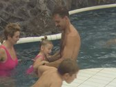 Father lifting little girl out and into pool Stock Footage