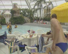 Man covering sleeping child with towel by poolside Stock Footage