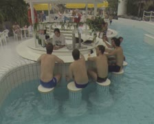 Men sitting in pool having drinks at a bar Stock Footage