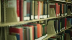 Student in library, pulling book off shelf Stock Footage