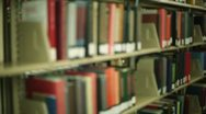 Stock Video Footage of Student in library, pulling book off shelf
