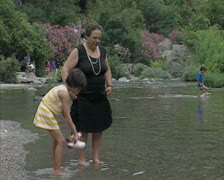 Child and woman walking throgh pool Stock Footage