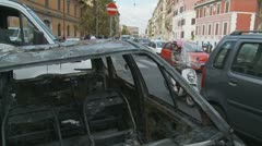 Glidecam out of burnt car from Rome riot Stock Footage