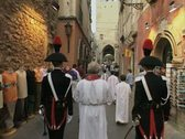 Priest and procession walking down street Stock Footage