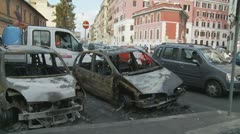 Glidecam into burnt out car (after Rome riot) Stock Footage