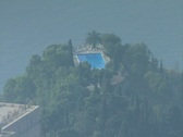 Stock Video Footage of Zoom out from swimming pool on hilltop to town