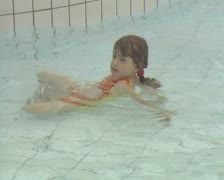 Little girl standing up and walking in pool Stock Footage