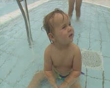 Close up of little boy sitting in pool Stock Footage