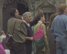 Tourists watching and talking as church bells chime Stock Footage