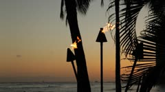 Tiki torch flames with sunset sky - stock footage