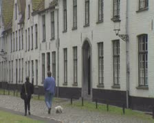 Row of white houses in quiet Beguinage area with couple walking past Stock Footage