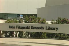 Zoom out from sign of John Fitzgerald Kennedy Library to full building Stock Footage