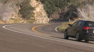 Stock Video Footage of Car accelerates through mountain curve.
