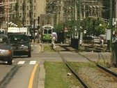 Moving car traffic beside tram line Stock Footage