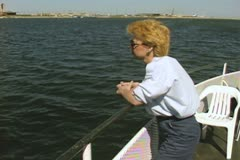 Woman leaning against boat railing Stock Footage
