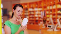 pensive woman looking at product in pharmacy - stock footage