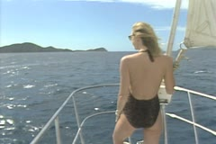 Woman leaning against catamaran railing viewed from rear Stock Footage