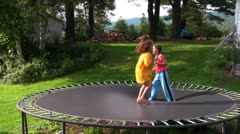 Kids jump and play on the trampoline in the backyard. - stock footage