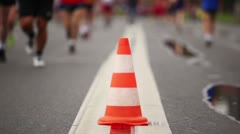 Big orange cone on road between running people Stock Footage