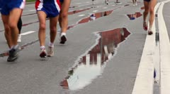 People run in sport wear and jogging shoes on wet asphalt with road marking Stock Footage