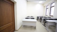 Empty classroom with wooden school desks and simple black chairs Stock Footage