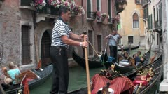 Gondolas take people through a narrow canal with buildings on each side in Stock Footage