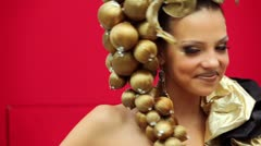Young model with hairdo with bunch of berries wear gold dress Stock Footage